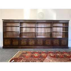 Late Victorian country house mahogany, walnut and oak dwarf breakfront bookcase, projecting cornice over frieze inlaid with figured walnut panels over eight open adjustable shelves, four fielded panelled double cupboard doors under enclosing four fixed shelves, raised on plinth base