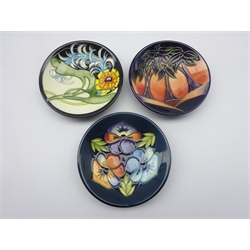 Three Moorcroft Collectors Club coasters - 'Triple Choice' & 'New Forest' both designed by Rachel Bishop 2005 & 2006 and 'Plume' by Emma Bossons, 2007, D12cm, all boxed (3)