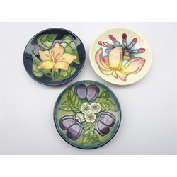 Three Moorcroft coasters - 'Frangipani' by Emma Bossons, Damsons trial piece & another trial piece decorated with a Lily, all dated 1999, D11.5cm (3)