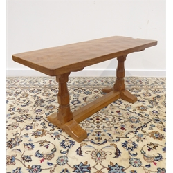 'Mouseman' oak coffee table with rectangular adzed top, octagonal supports on sledge feet joined by floor stretcher, by Robert Thompson of Kilburn, 92cm x 38cm, H45cm