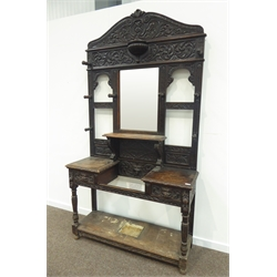 Large late Victorian heavily carved oak hall stand, scrolled acanthus leaf decoration, central bevel edged mirror, eight turned coat pegs, two drawers carved with lion mask handles, central umbrella stand, W127cm, H232cm, D44cm