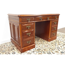Late 19th century walnut twin pedestal desk, fitted with nine graduating drawers, inset writing surface, brass drop handles, panelled sides and back, W124cm, D66cm, H75cm