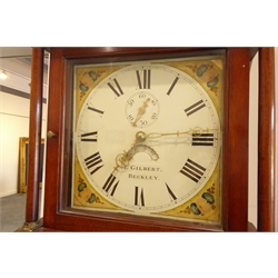 Early 19th century 30 hour mahogany long case clock by T Gilbert of Beckley, swan neck pediment, enamel face with painted floral spandres, seconds ring and date aperture, hammer striking the quarters on bell, long figured door, bracket feet, H201cm
