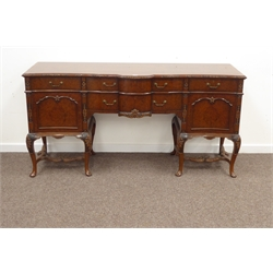 Queen Anne style burr walnut serpentine sideboard, cross banded top with carved and moulded edge, above two long and two short drawers and two paneled cupboards, on cabriole supports with further floral relief carving W182cm, H92cm, D60cm