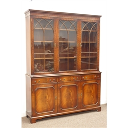 Quality reproduction mahogany bookcase on cupboard, projecting dentil cornice over three astragal glazed doors, three drawers and three paneled cupbo