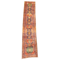 Large Persian Karajeh red ground runner, eight lozenges in green blue and red, decorated with geometric patterns on a red field, guarded boarder with