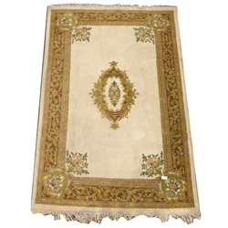 Indian design beige ground rug, floral medallion, guarded boarder (187cm x 286cm) together with a similar oval ground rug (160cm x 150cm)