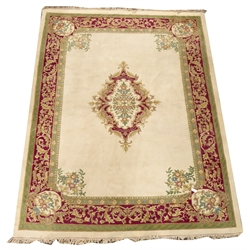 Large Indian design wool beige ground rug, central floral medallion on beige field, green red and brown guarded boarder with scrolled foliate decorat