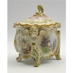 Effra Berlin KPM jar and cover in the form of a bough pot and cover painted with a cottage and figure in foreground with a further landscape to the back signed 'Jackel' with winged cherub mount on scroll feet H22cm x W14cm