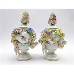 Pair of Sitzendorf vases and covers decorated with applied flowers and cherubs H26cm