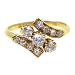 Edwardian 18ct gold three stone diamond crossover ring, with diamond set shoulders, Birmingham 1902