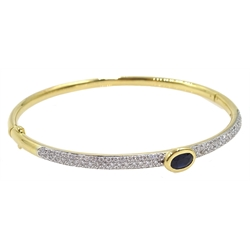 18ct gold hinged bangle, with a central rim set oval sapphire and pave set diamonds either side, stamped 750, sapphire 0.65 carat, diamonds 0.89 carat
