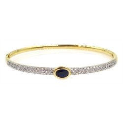 18ct gold hinged bangle, with a central rim set oval sapphire and pave set diamonds either side, stamped 750, sapphire 0.65 carat, diamonds 0.89 cara