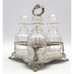 19th Century plated 4 bottle decanter stand of serpentine with floral chased loop handle with 4 glass decanters