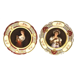 Pair of early 20th Century Vienna style porcelain plates each decorated with a female figure holding a candlestick and titled to the reverse 'Lisette' and 'Gute Nacht' within a floral gilded border with panels of cherubs D24cm