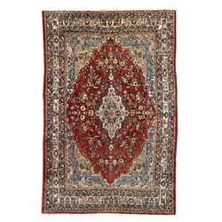 Large central Asian ground rug, lozenge medallion on red field, blue and beige spandrels, triple guarded border decorated with trailing foliate, 260c