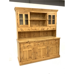 Large solid pine dresser, moulded cornice above two open shelves, two glazed doors and six drawers, rectangular top to base over three drawers and th