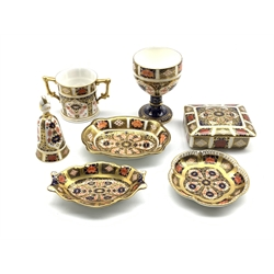 Royal Crown Derby Imari 1128 pattern ceramics comprising three small dishes, lidded trinket box, chalice, bell and a loving cup (7)