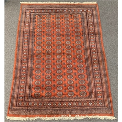 Persian design Bokhara ground carpet, repeating gul motif on burnt orange field, guarded border, 31cm x 218cm