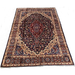 Persian Meshed blue ground carpet, with medallion and interlaced trailing foliate on blue field, floral spandrels, triple guarded border, 305cm x 415cm