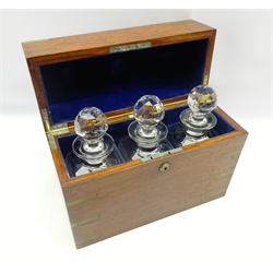Early 20th century oak and brass bound decanter box by Army & Navy, containing three faceted glass decanters, L35cm x H28cm