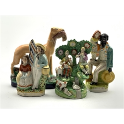Early 19th Century Staffordshire figure group in the style of Walton of male and female musicians in bocage H21cm, another of a standing greyhound holding a hare H25cm and two other 19th Century Staffordshire figures