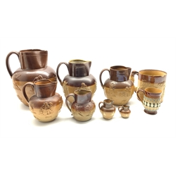 Group of six Doulton Lambeth stoneware harvest jugs, the two smallest with silver rims, largest H25cm, another, unmarked, a Stoneware hunting mug and a Royal Doulton mug (9)