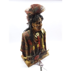 Large half length sculpture of 'Dandy' a Native American Blackfoot warrior, the composite body dressed in typical clothing with beaded necklaces and porcupine style headdress on carved hardwood base, H92cm