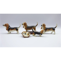 Three Beswick Basset Hound models, Royal Doulton Cocker Spaniel in basket and a Goebel Basset Hound (5)