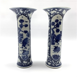 Pair of Chinese blue and white cylindrical vases, painted with Buffalo within moulded panels on a cell-ground reserved with butterflies with incised details, H28.5cm