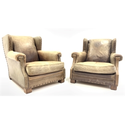 Ralph Lauren for Harrods - Pair of deep wingback club armchairs upholstered in studded green tan leather, raised on block supports, W88cm, H80cm, D111cm
