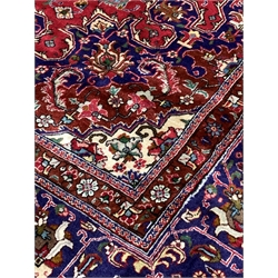 Large Persian fine Tabriz red ground carpet, central medallion on busy red field, with stylised foliate to multi line border, 406cm x 304cm