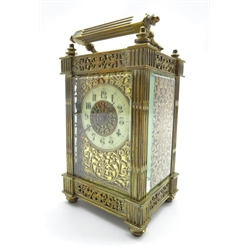 Late 19th century brass carriage clock, circular Roman enamel dial, pierced floral scrolling brass panels with engraved flower head detail, fluted uprights and hinged carrying handle, eight day movement with platform escapement, H15.5 (including handle)