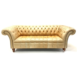 Late 20th century three seat Chesterfield sofa, upholstered in deep buttoned tan leather, raised on turned walnut supports, W221cm, H78cm, D105cm