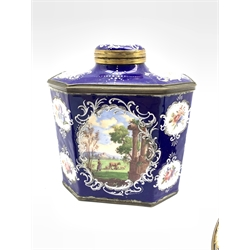 Late 18th century Bilston enamel octagonal tea caddy, the blue ground decorated with Rococo style white enamel cartouches containing landscape scenes with figures and animals together with a pair of matching candlesticks, H27cm