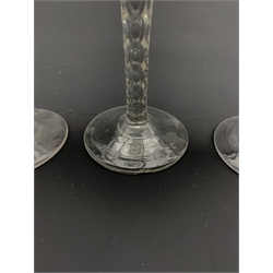 Set of three 18th century wine glasses, the ovoid bowls engraved with flower sprigs on faceted stems and conical feet, H15cm