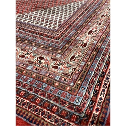 Large Persian Araak carpet, red ground field decorated all over with Boteh motifs, multiple band border, 420cm x 319cm