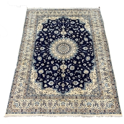 Persian ivory ground carpet, central medallion on blue field decorated with interlaced foliate