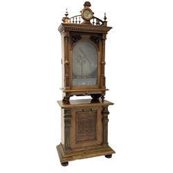 Victorian walnut penny-in-the-slot polyphon music box, the pediment with HAC time piece clock over dentil cornice, two turned and fluted pilasters enclosing the arched glazed door with pierce carved ribbons and scrolled acanthus leaf decoration, the mechanism with winding handle and two combs intact, drawer under, all raised on a later fall front bin containing twenty-four 63cm diameter records H252cm, W89cm, D49cm