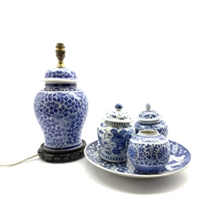 Early 20th Century Japanese shallow dish decorated with prunus in blue and white D31cm, two 20th Century Chinese blue and white jars and covers H17cm, another without lid and a vase column table lamp