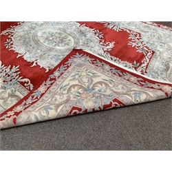 Chinese woolen ground rug, floral medallion on red field, border with scrolled foliate, 227cm x 393cm