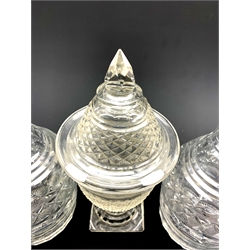 Regency cut glass sweetmeat jar and cover, hobnail cut body, domed cover on terraced square foot H25cm, together with a pair of early 19th century faceted glass mallet form decanters (3)