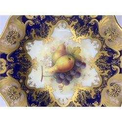 Royal Worcester porcelain twin-handled comport painted by Albert Shuck, signed, with grapes and pears, the border with six shaped cartouches in pink applied in gilt with leafy scrolls jewelled in gilt, on a cobalt blue ground, L33cm x H14.5cm