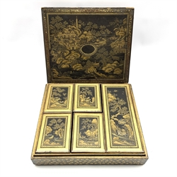19th century Chinese black lacquer and gilt games box, of rectangular form, the body decorated with landscapes within stylised foliate borders, the cover opening to reveal an interior fitted with five lidded boxes containing mother of pearl counters, the majority engraved with the initials E.W. and the remaining engraved with Pagodas, together with stained ivory counters, L30cm, D26.5cm, H8cm