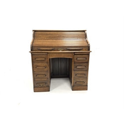 Edwardian oak serpentine roll top desk with fitted interior over central drawer flanked by a pair of pedestals with filing drawer, W107cm, H112cm, D66cm