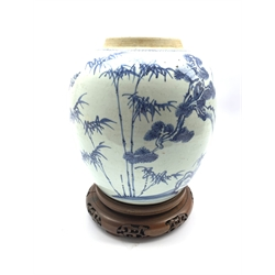 18th century Chinese Provincial blue and white ginger jar decorated with tree and sprays of bamboo among rocks, later hardwood stand and cover, H23cm
