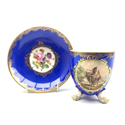 19th century Meissen cabinet cup and saucer, the cup painted in the manner of Wouwerman with a pastoral scene on blue ground, serpent moulded handle and paw feet, H9.5cm