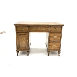 Late Victorian golden pine twin pedestal desk, skivered top over four drawers and a cupboard, incised decoration and brass Gothic style handles, raised on turned supports with brass collared ceramic castors, W115cm, H80cm, D61cm
