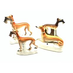 Three 19th century Staffordshire Greyhound models holding a in their mouths and another with pen stand base, H20cm max (4)